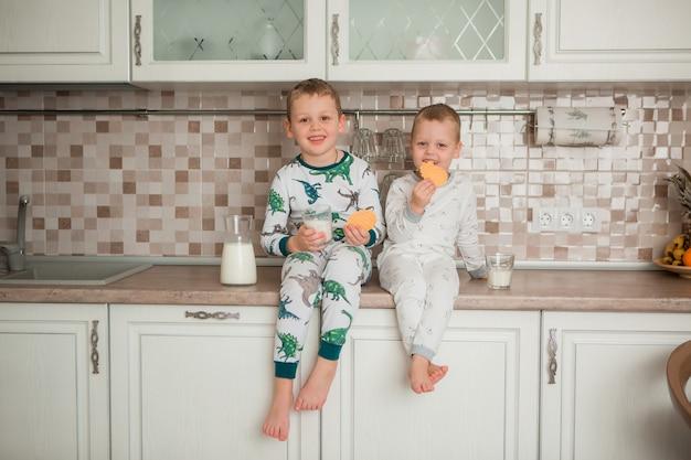 Deux garçons prennent leur petit déjeuner dans la cuisine Photo Premium