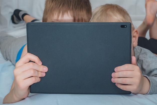 Deux Garçons Sont Couchés Et Regardent La Tablette Photo Premium