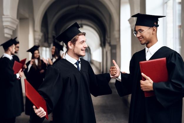 Deux gars en robe parlent à l'université. Photo Premium