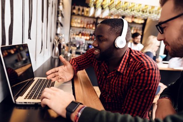 Deux gars sont assis au bar avec un ordinateur. Photo Premium