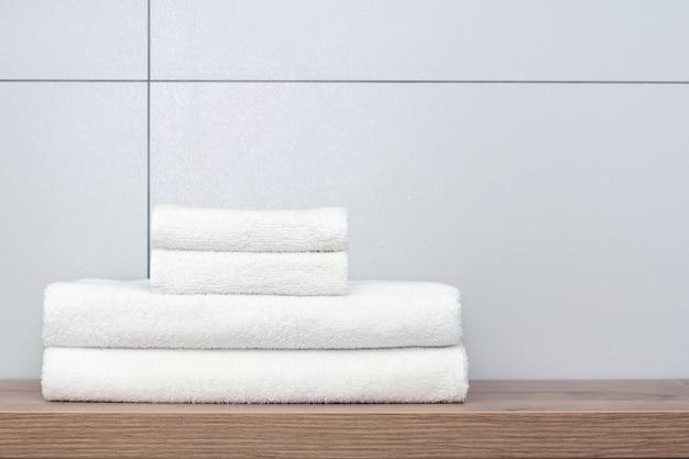 Deux grandes et deux petites serviettes blanches soigneusement pliées reposent sur une étagère en bois sur le fond de carreaux de céramique. Photo Premium