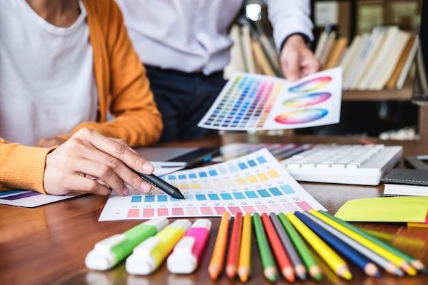 Deux graphistes créatifs travaillant avec des collègues sur la sélection des couleurs et des échantillons de couleurs Photo Premium