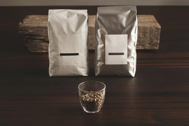 Deux Gros Emballages Hermétiques Avec Des étiquettes Vierges Près De Verre Transparent Avec Des Grains De Café Crus échantillonnés Photo gratuit