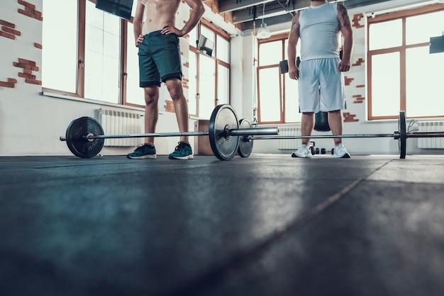 Deux gros joueurs se tiennent dans la salle de sport devant les barreaux. Photo Premium