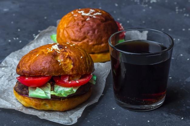 Deux Hamburgers Au Bœuf Grillé Avec Laitue Et Tomates Et Verre De Boisson Non Alcoolisée Photo Premium