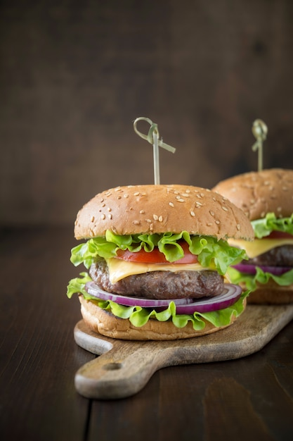 Deux hamburgers de boeuf frais avec des légumes sur une planche de bois Photo Premium