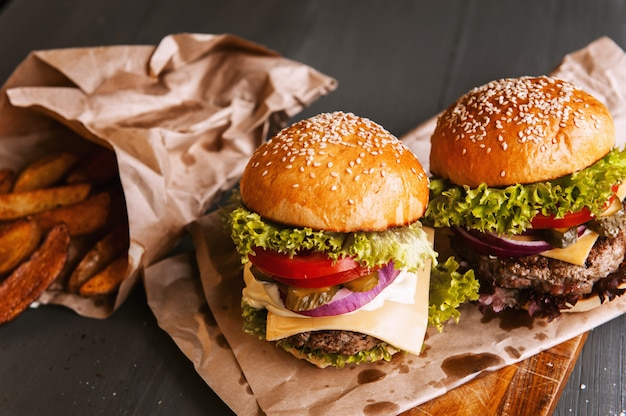 Deux hamburgers faits maison délicieux et appétissants utilisés pour hacher le bœuf. sur la table en bois. Photo Premium