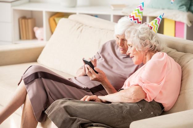 Deux Hauts Femaled En Casquettes D'anniversaire Assis Sur Un Canapé Tout En Discutant De Choses Curieuses Dans Un Smartphone Photo Premium