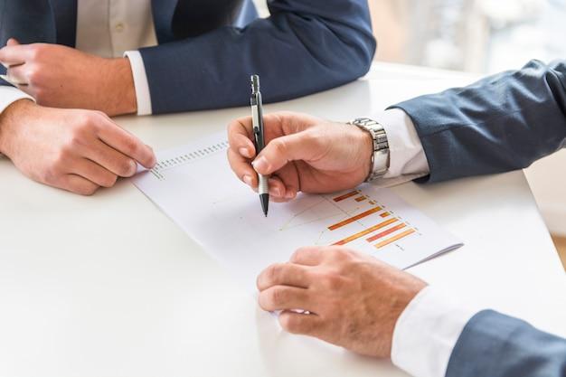 Deux homme d'affaires analysant le rapport d'activité sur le bureau blanc Photo gratuit