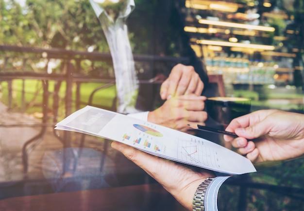Deux homme d'affaires discutant de leur rapport dans un café Photo gratuit
