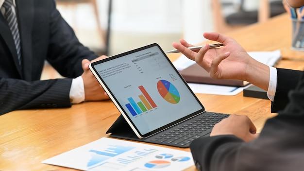 Deux homme d'affaires rencontre et consulte un ordinateur portable numérique sur la table. Photo Premium