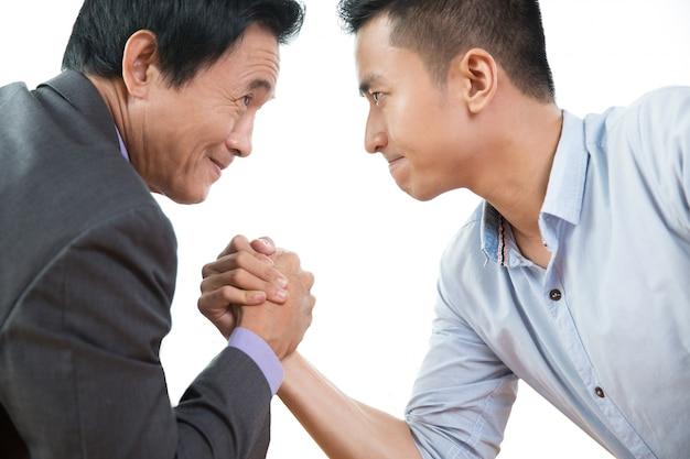 Deux hommes d'affaires arm wrestling obstinément, gros plan Photo gratuit
