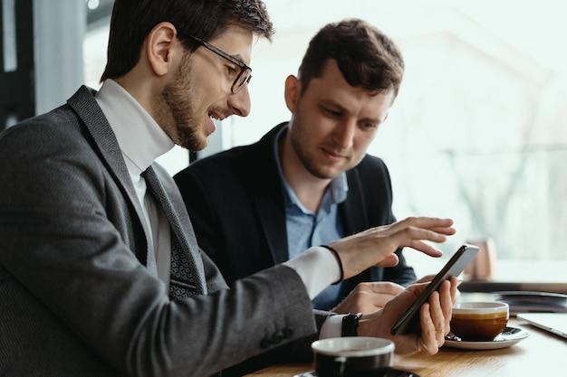 Deux Hommes D'affaires Ayant Une Conversation à L'aide D'un Smartphone Photo gratuit
