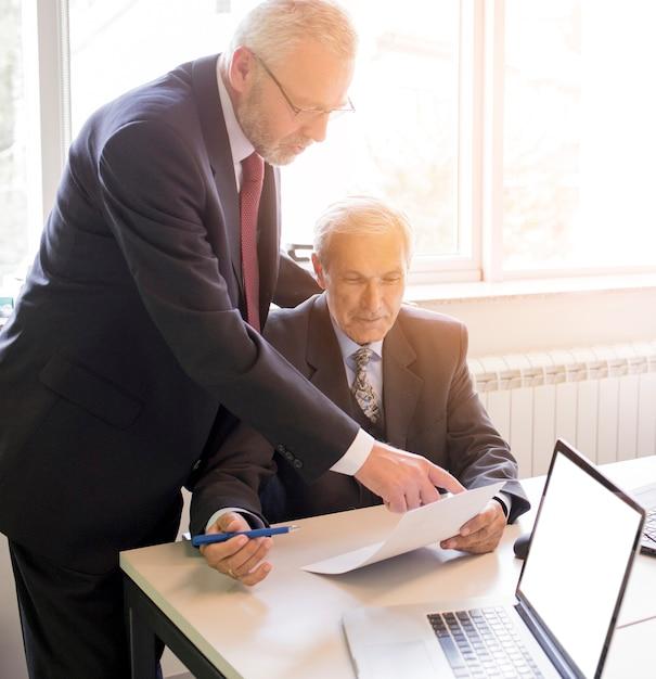 Deux hommes d'affaires mature discutant d'un projet professionnel au bureau Photo gratuit