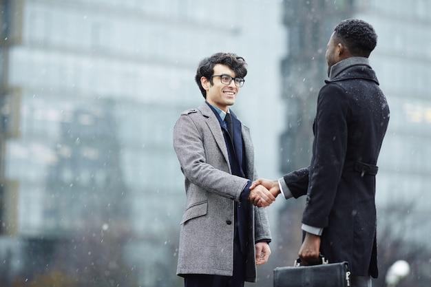 Deux hommes d'affaires réunis dans la rue Photo gratuit
