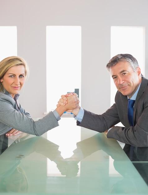 Deux hommes d'affaires souriants ayant une épreuve de force assis autour d'une table Photo Premium