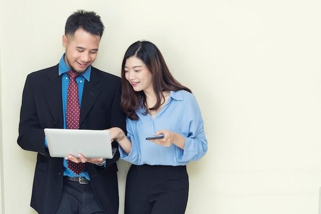 Deux hommes d'affaires utilisant un téléphone portable et un ordinateur portable. Photo Premium