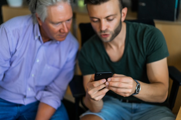 Deux hommes d'âges différents au bureau, partenaires commerciaux Photo gratuit