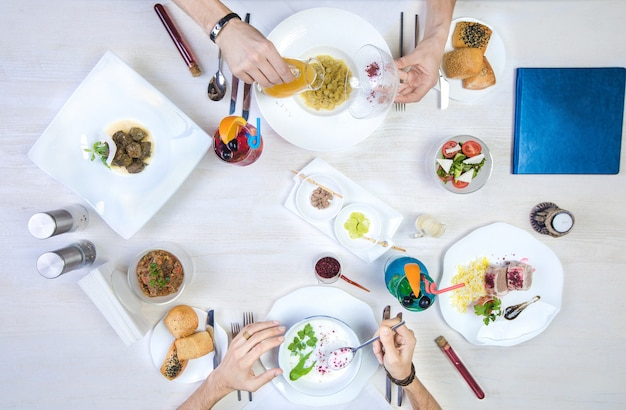 Deux hommes déjeunant avec dushbara, dovga, dolma, riz et poulet Photo gratuit