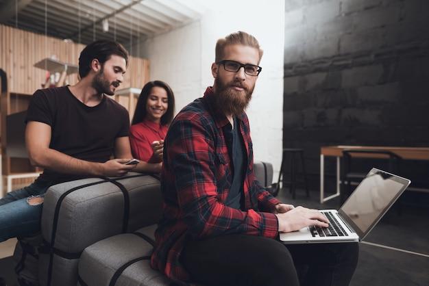 Deux hommes et une femme sont assis sur les coussins. Photo Premium