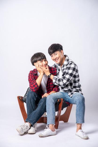 Deux Hommes Qui S'aiment S'embrassent Et S'assoient Sur Une Chaise. Photo gratuit