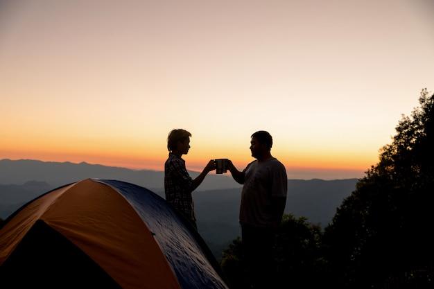 Deux hommes touristes heureux au sommet de la montagne près du feu de camp Photo gratuit