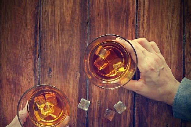 Deux hommes trinquent avec des verres de whisky buvant une boisson alcoolisée ensemble au comptoir du bar du pub. Photo Premium