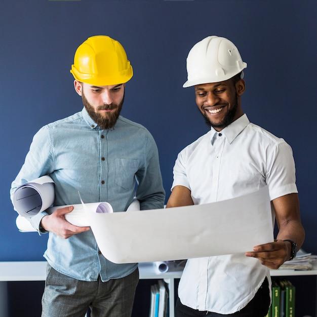Deux ingénieurs masculins regardant blueprint Photo gratuit