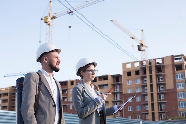 Deux ingénieurs travaillant sur un chantier de construction Photo gratuit