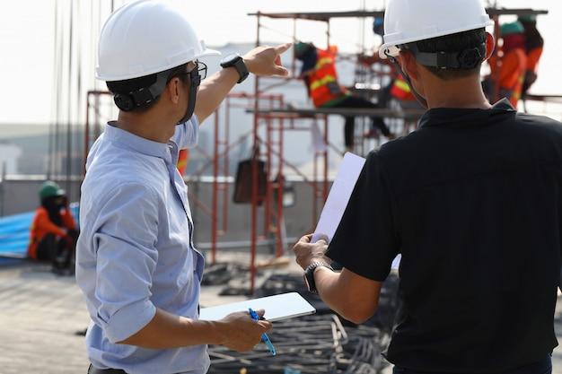Deux Ingénieurs Travaillent Sur Le Chantier. Ils Vérifient L'avancement Des Travaux. Photo Premium