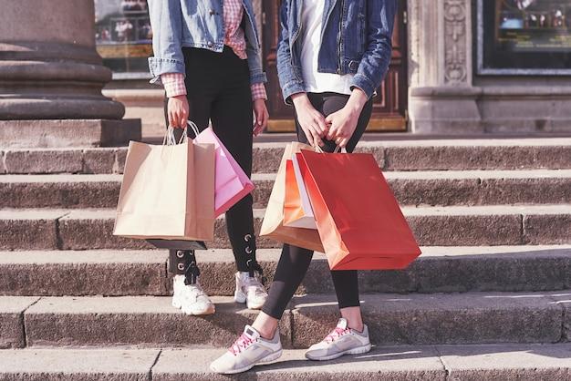 Deux Jeune Femme Portant Des Sacs En Marchant Dans Les Escaliers Après Avoir Visité Les Magasins. Photo gratuit