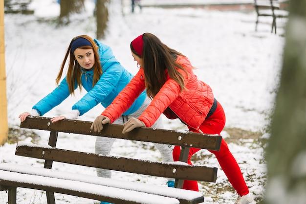Deux jeune femme qui s'étend près du banc en hiver Photo gratuit