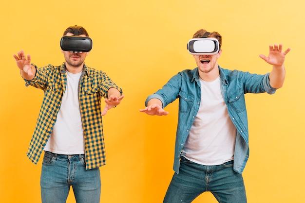 Deux, jeune homme, utilisation, lunettes de réalité virtuelle, toucher, air, contre, jaune, fond Photo gratuit