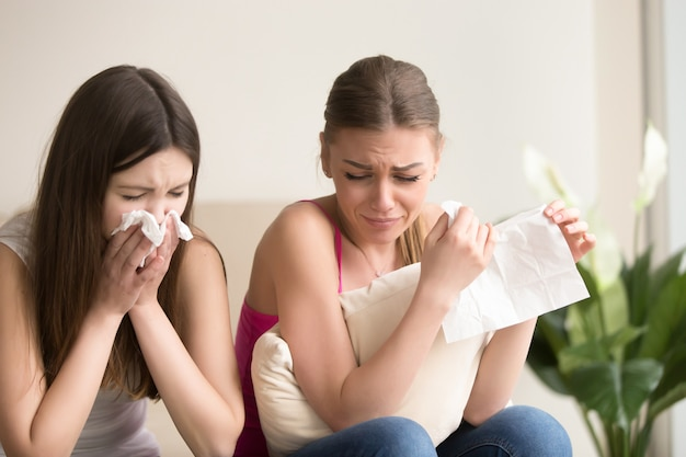Deux jeunes amies pleurant ensemble à la maison Photo gratuit