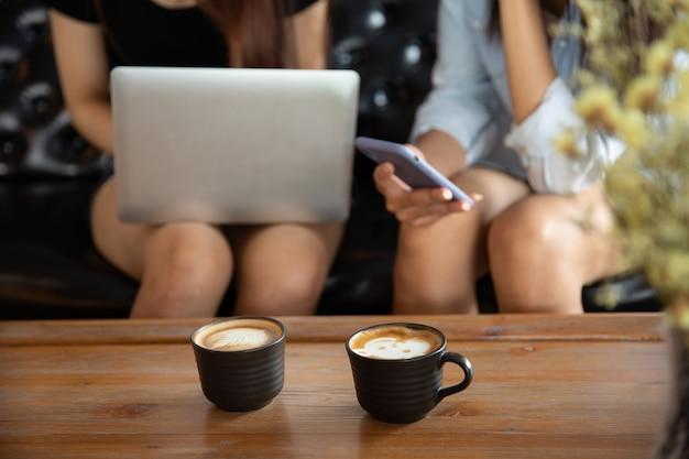 Deux jeunes amies avec le smartphone sur la main parler et boire assis sur un canapé dans le café café. Photo Premium