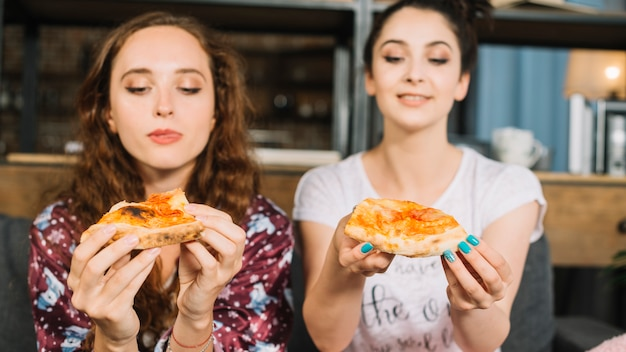 Deux jeunes amies tenant une tranche de pizza Photo gratuit