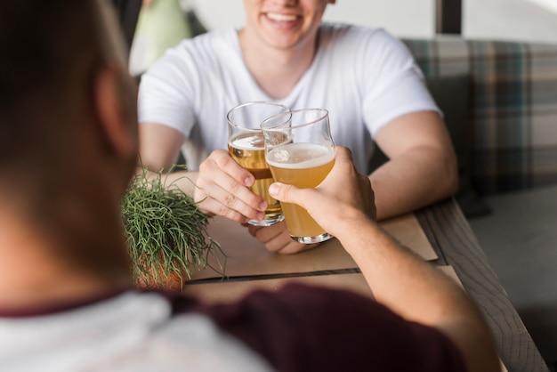 Deux jeunes amis grillage des verres de bière Photo gratuit