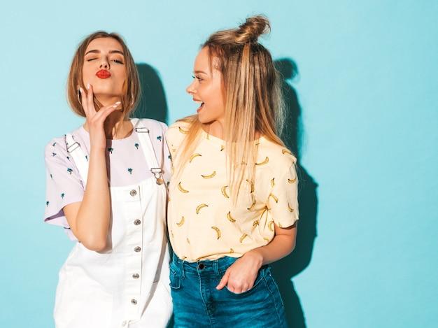 Deux Jeunes Belles Filles Blondes Blondes Souriantes Dans Des Vêtements De T-shirt Coloré D'été à La Mode. Et Donner Un Baiser Photo gratuit