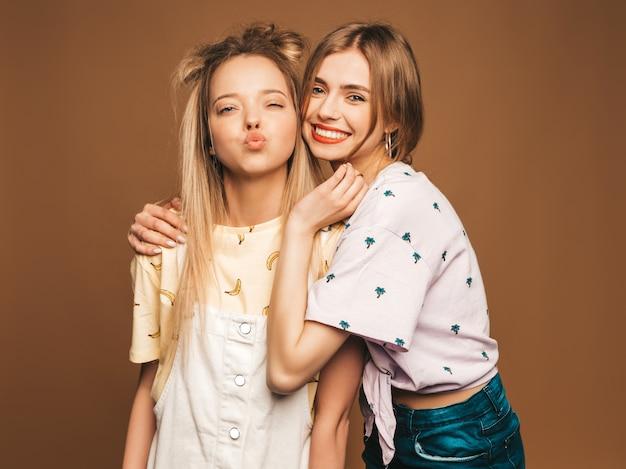 Deux Jeunes Belles Filles Blondes Blondes Souriantes Dans Des Vêtements De T-shirt Coloré D'été à La Mode. Femmes Insouciantes Sexy Posant Sur Fond Beige. Modèles Positifs Donnant Un Baiser Photo gratuit