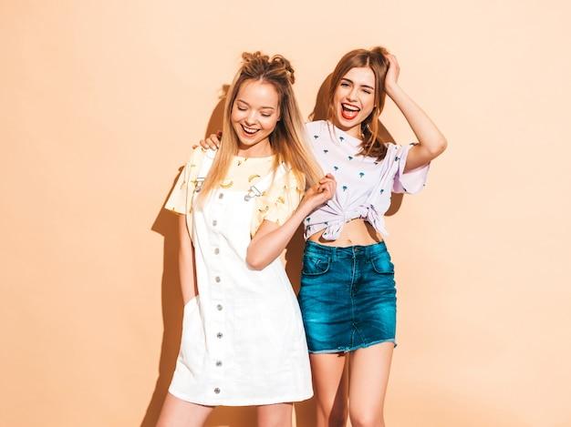 Deux Jeunes Belles Filles Blondes Blondes Souriantes Dans Des Vêtements De T-shirt Coloré D'été à La Mode. Et Montrant La Langue Photo gratuit