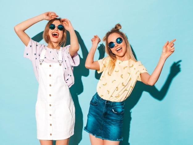 Deux Jeunes Belles Filles Blondes Blondes Souriantes Dans Des Vêtements De T-shirt Coloré D'été à La Mode. Photo gratuit