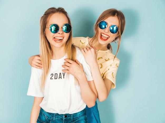 Deux Jeunes Belles Filles Blondes Hipster Blond Souriant Dans Des Vêtements Colorés D'été à La Mode. Photo gratuit