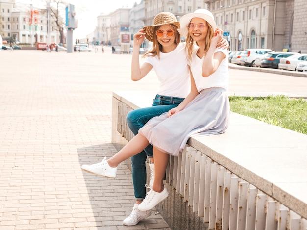 Deux Jeunes Belles Filles Blondes Souriantes Hipster En Vêtements De T-shirt Blanc à La Mode D'été. Femmes Insouciantes Sexy Assis Sur Fond De Rue. Photo gratuit