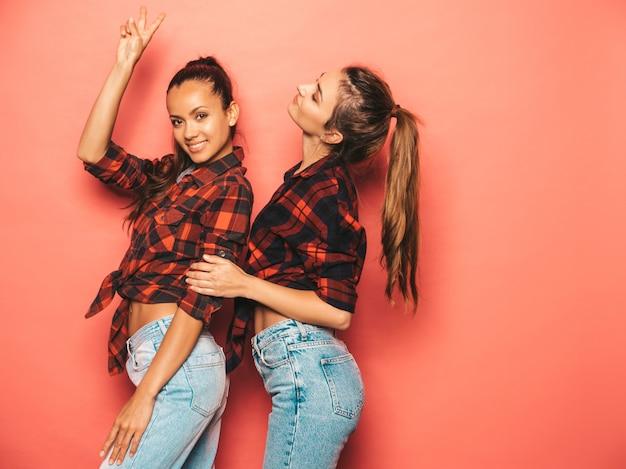Deux Jeunes Belles Filles Hipster Brune Souriante Dans Une Chemise à Carreaux Similaire à La Mode Et Des Vêtements En Jeans.des Femmes Insouciantes Sexy Posant Près Du Mur Rose En Studio.des Modèles Positifs S'amusant Photo gratuit