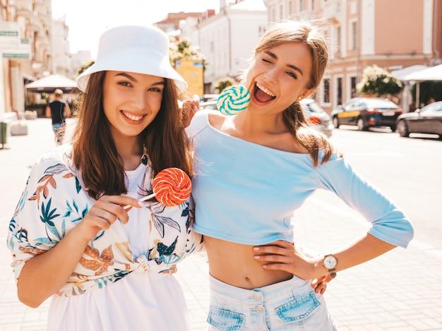 Deux Jeunes Belles Filles Hipster Souriantes Dans Des Vêtements D'été à La Mode Et Un Chapeau Panama. Photo gratuit