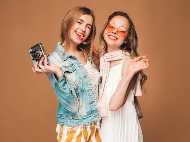 Deux Jeunes Belles Filles Souriantes Dans Des Vêtements Décontractés D'été à La Mode Et Des Lunettes De Soleil. Femmes Insouciantes Sexy Posant. Prendre Des Photos Sur Un Appareil Photo Rétro Photo gratuit