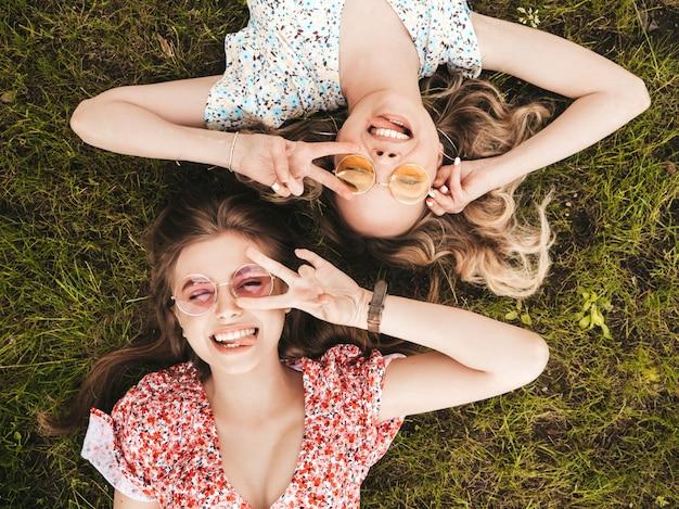Deux Jeunes Belles Filles Souriantes Hipster En Robe D'été à La Mode.des Femmes Insouciantes Sexy Allongées Sur L'herbe Verte Dans Des Lunettes De Soleil.des Modèles Positifs S'amusant.vue De Dessus.ils Montrent Le Signe De La Paix Photo gratuit