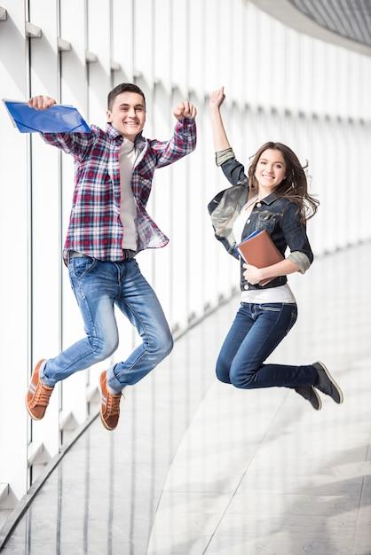Deux jeunes étudiants heureux sautant au collège. Photo Premium