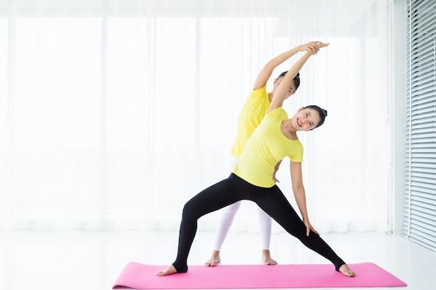 Deux jeunes femmes asiatiques s'entraînent au yoga en robe jaune ou posent avec un entraîneur et pratiquent Photo Premium