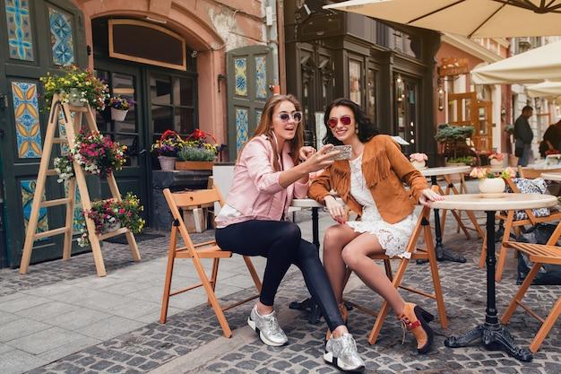 Deux Jeunes Femmes Belles Hipster Assis Au Café Photo gratuit
